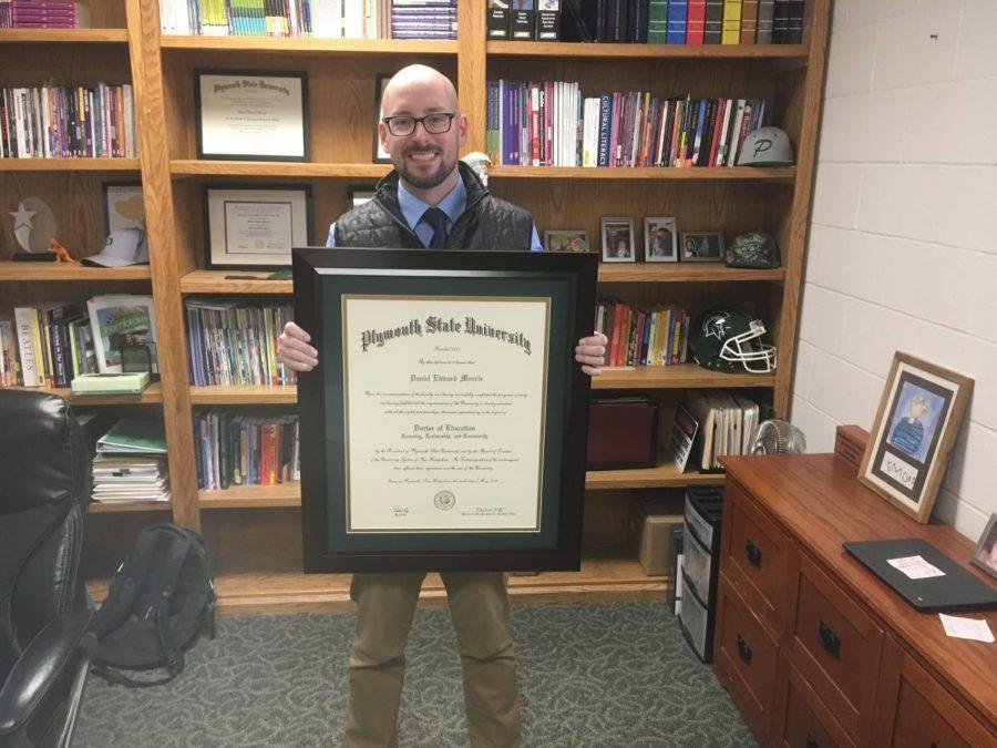 Mr. Morris holding his Ed.D diploma.